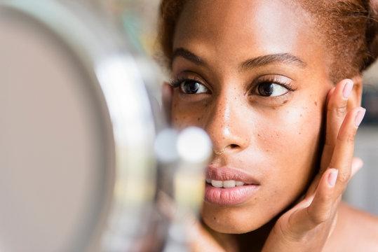Women looking at skin in mirror