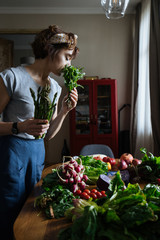 Woman in kitchen with fresh vegetables on table