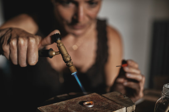 Female jeweler using her torch to shape a ring