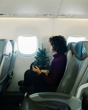 Woman with Christmas tree looking at the window of the airplane