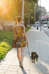 Girl Walking With Her Dog On The Streets.