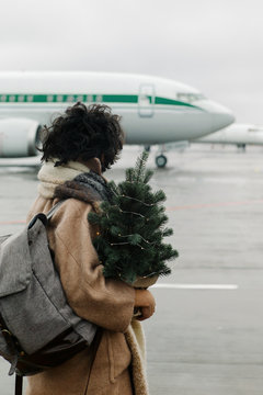 Portrait of a curly girl with a Christmas tree in front of an airplane