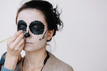 Unrecognizable female creating face art with halloween skull