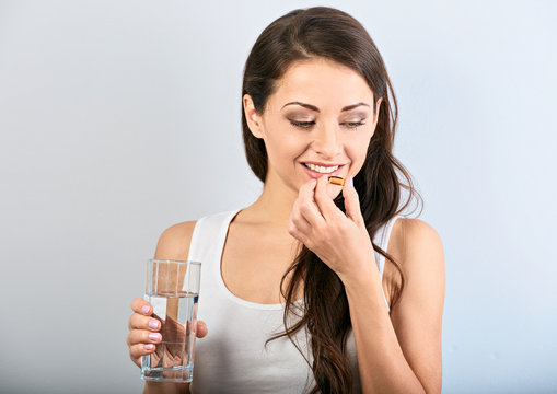 Happy smiling positive woman eating the pill and holding the glass of water in the hand on blue background. Closeup