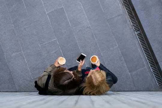 Unrecognizable women using a mobile in the street