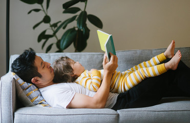 Side view of father and daughter reading book on sofa at home