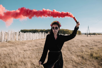 Halloween portrait of woman wearing black with red smoke