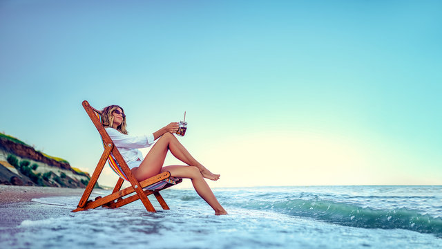 Pretty woman relaxing on a lounger beach and drinks soda water. summer vacation concept.