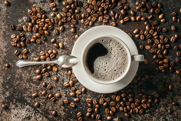 Fototapete - Coffee cup and coffee beans on dark stone background. .