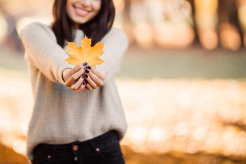 Beautiful woman posing for the camera with autumn leaf. Happy Autumn.
