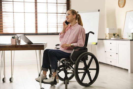 Woman in wheelchair talking on phone at table indoors