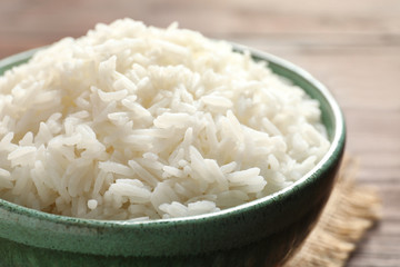 Bowl of tasty cooked white rice on table, closeup
