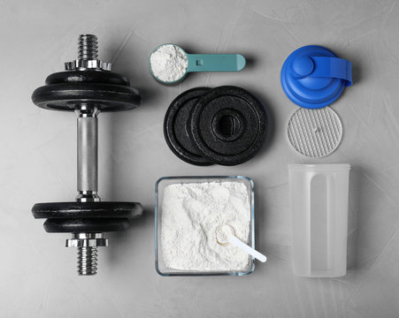 Flat lay composition with protein powder and dumbbell on grey background