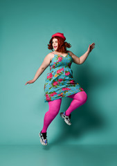 Overweight woman in funny hat, colorful sundress and tights jumps funny or runs away from something on mint