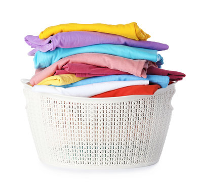 Plastic laundry basket with clean clothes on white background