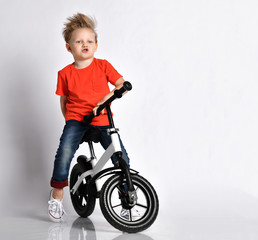 Young kid boy in orange t-shirt and blue jeans imagines he rides fast his new cool bicycle without pedals. Imitates engine sound