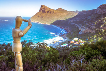 View of steep mountain cliffs joining onto a beach with houses on the slopes, with little wooden manikin posing, Cape Town, South Africa