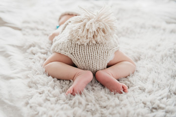 Adorable newborn is sleeping butt -up in cute knitted outfit on fluffy blanket