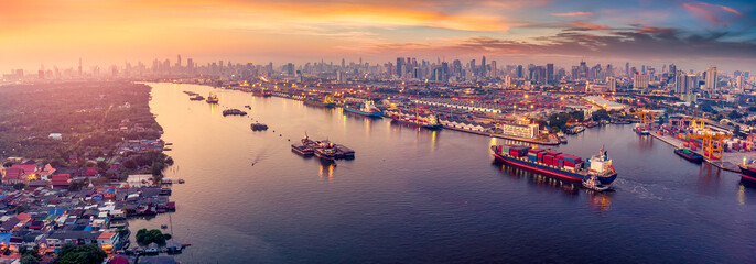 Wall Mural - Panoramic Logistics and transportation of Container Cargo ship and Cargo plane with working crane bridge in shipyard at sunrise, logistic import export and transport industry background