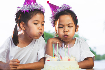 Two asian child girls celebrating birthday and blowing candles on birthday cake in the party