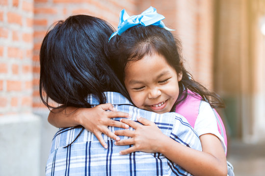 Back to school. Cute asian pupil girl with backpack hugging her mother with happiness after back from school