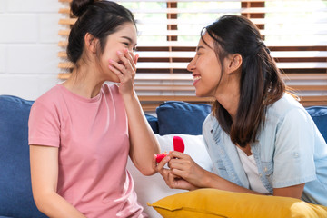 Happy asian couple lesbian proposal with ring for marry at living room at home.LGBTQ lifestyle concept.