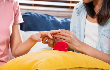 close up asian couple lesbian wearing proposal ring for marry at living room at home.LGBTQ lifestyle concept.