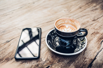 Close up hot black coffee cup and mobile on wood table near window with sunlight at cafe restaurant.Leisure lifestyle.food and drink