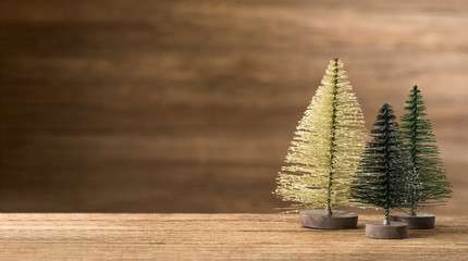 Christmas tree on wood table with wooden wall for merry chirstmas and new year holiday greeting card backgrond. banner mock up with copy space for display product.