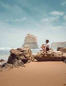 Tourist seated in a rock in a beach in the Twelve Apostles, near Melbourne, in Australia, with a bird near him