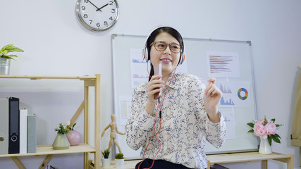 young beautiful asian woman office lady listen music by headphones in office relax dance in good mood. cute chinese female employee working in office in glasses hold cellphone singing as microphone