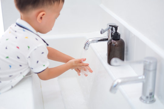 Cute little Asian 2 - 3 years old toddler boy child washing hands by himself on sink and water drop from faucet in public toilet / bathroom for kids, Clean school washrooms - soft & selective focus