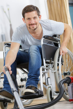 content man on wheelchair with vacuum cleaner