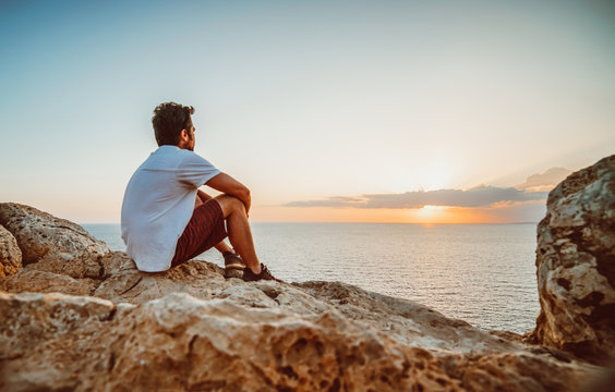 Lonely guy observing the sunset from a cliff in Cyprus