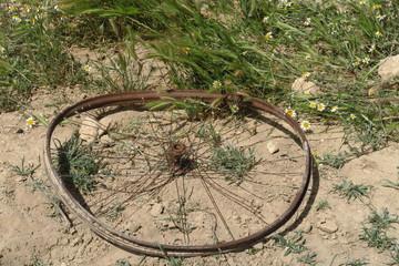 Roue de vélo rouillé sur la terre sèche.