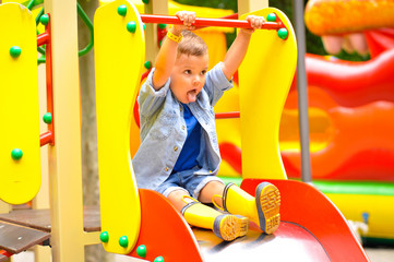 A little cute three-year-old boy plays on the playground and slides down the slides in yellow rubber boots.