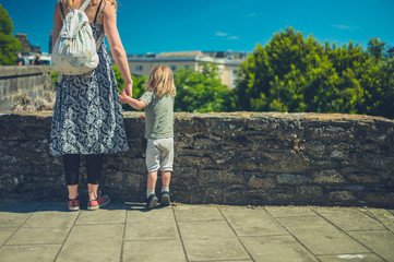 Young mother and toddler standing by stone wall