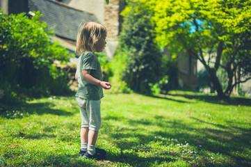 Little toddler standing on the grass in park