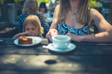 Young mother and toddler having coffee and cake