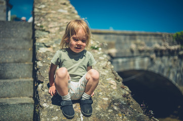 Little toddler sitting on wall near stone bridge