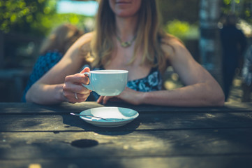 Woman drinking coffee in cafe outdoors