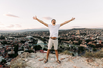 young man on the background of panoramic view of Tbilisi city.