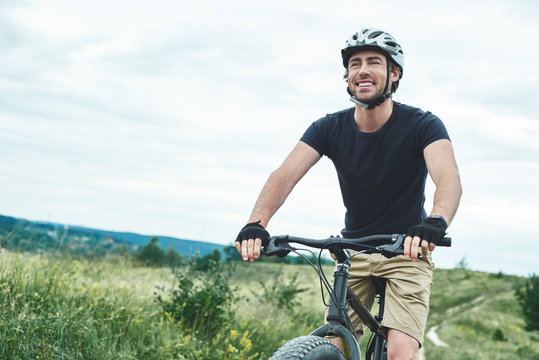 Attractive young man is cycling at the mountains. Cropped photo