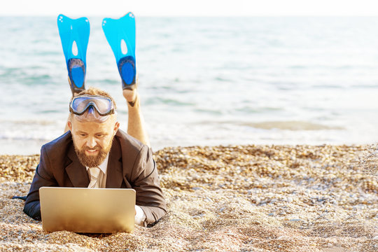 Successful businessman wearing snorkeling tools is working on the beach with laptop