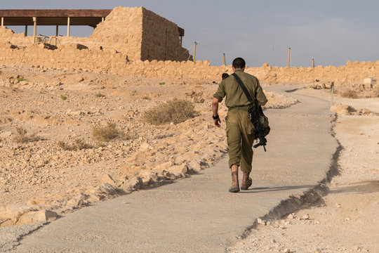 Back view of military going alone among deserted territory somewhere in the middle east. Masada fortification, Israel, war trainning. Tired soldier walking in desert after military mission. Conflict