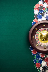 Casino Roulette Background with Roulette Drum,Casino Chips on Green Felt Table