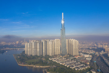 Top View of Building in a City - Aerial view Skyscrapers flying by drone of Ho Chi Mi City with development buildings, transportation, energy power infrastructure. include Landmark 81 and blue sky ,