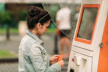 Tourist woman buys tickets for transport in Georgia. modern street machine for purchase of tickets for bus