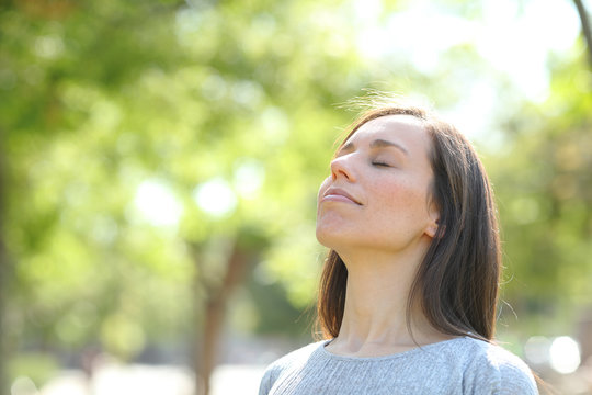 Relaxed woman breathing fresh air in a park or forest
