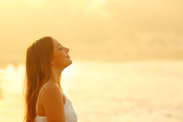Woman at sunset relaxing breathing fresh air